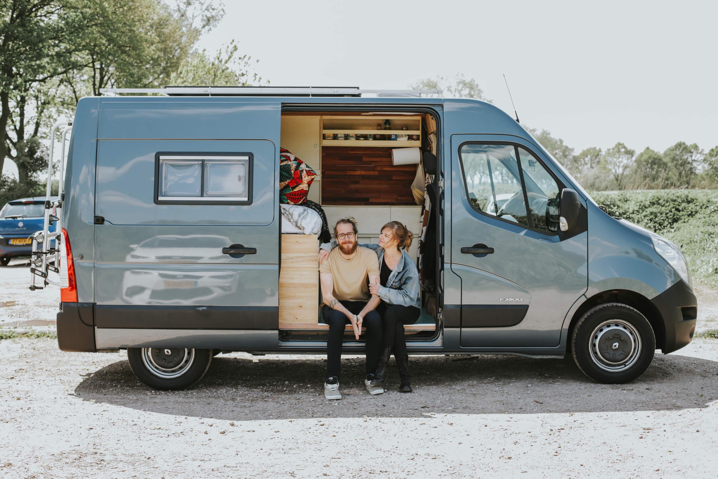 Man en vrouw zitten in de deuropening van hun camper.